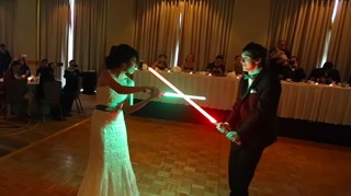Bride and groom have Star Wars lightsaber battle for first dance.
