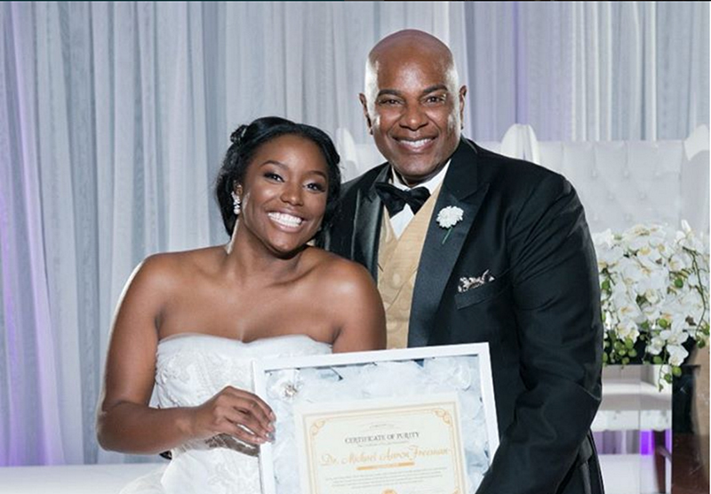 Bride poses with certificate of purity