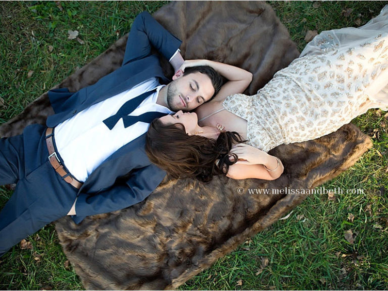 Jade Roper and Tanner Tolbert lay on fur blanket for engagement photos