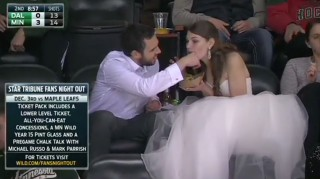 Bride eating a burger at a hockey game in wedding dress