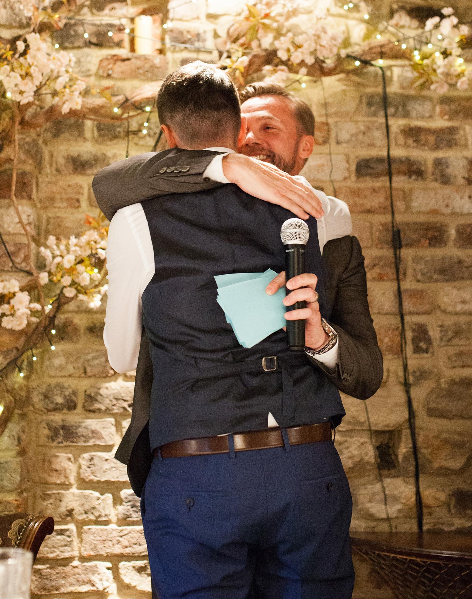 Groom hugging best man afters peech