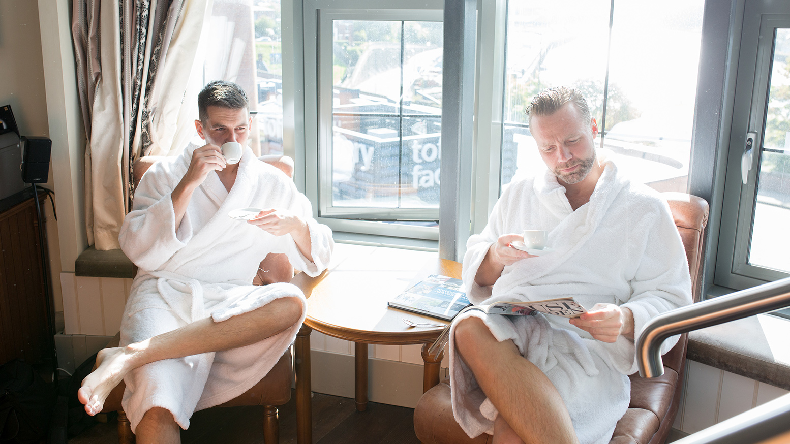 Groom and best man drinking coffee in robes