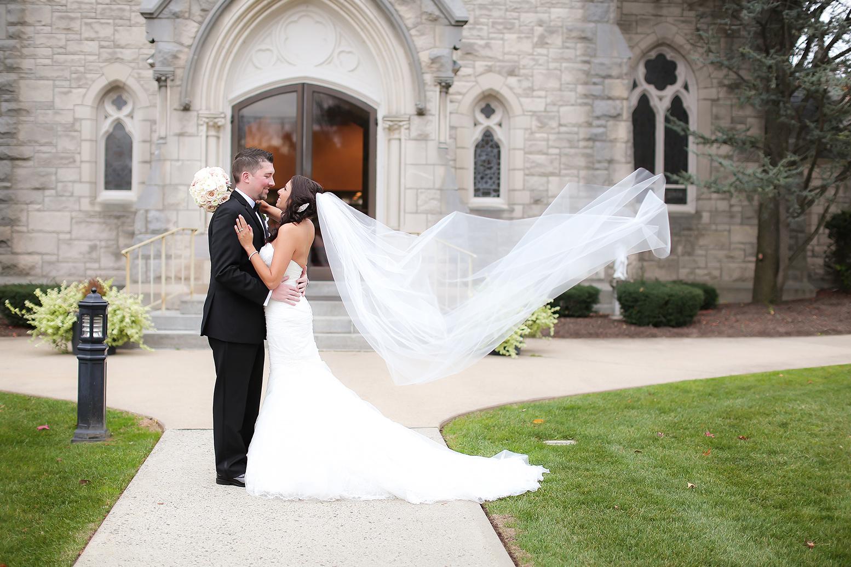 Groom Brian Kurtulik and bride Lauren posing outside church