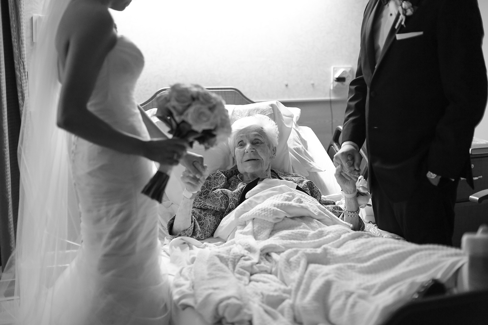 Bride and groom holding their grandmother's hand