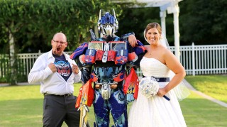 Melissa and Kenny pose with Optimus Prime at their transformers wedding
