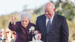 Grandma flower girl tossing petals down wedding aisle