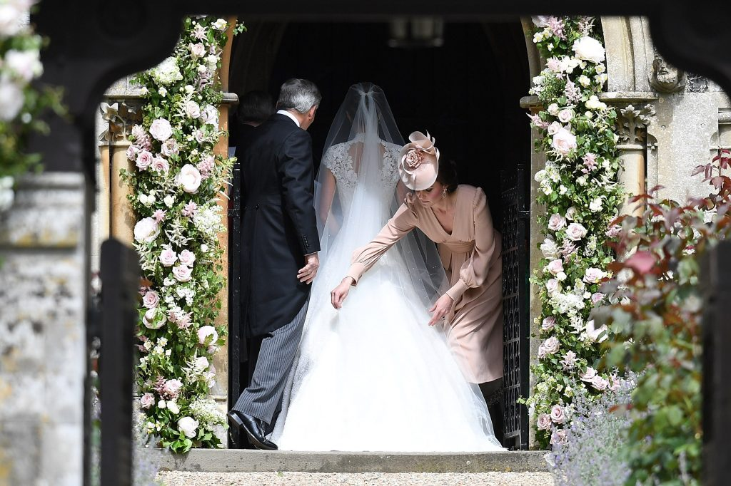 ENGLEFIELD GREEN, ENGLAND - MAY 20: Catherine, Duchess of Cambridge adjusts the dress of Pippa Middleton as she enters the church during the wedding of Pippa Middleton and James Matthews at St Mark's Church on May 20, 2017 in Englefield Green, England. (Photo by Samir Hussein/Samir Hussein/WireImage)