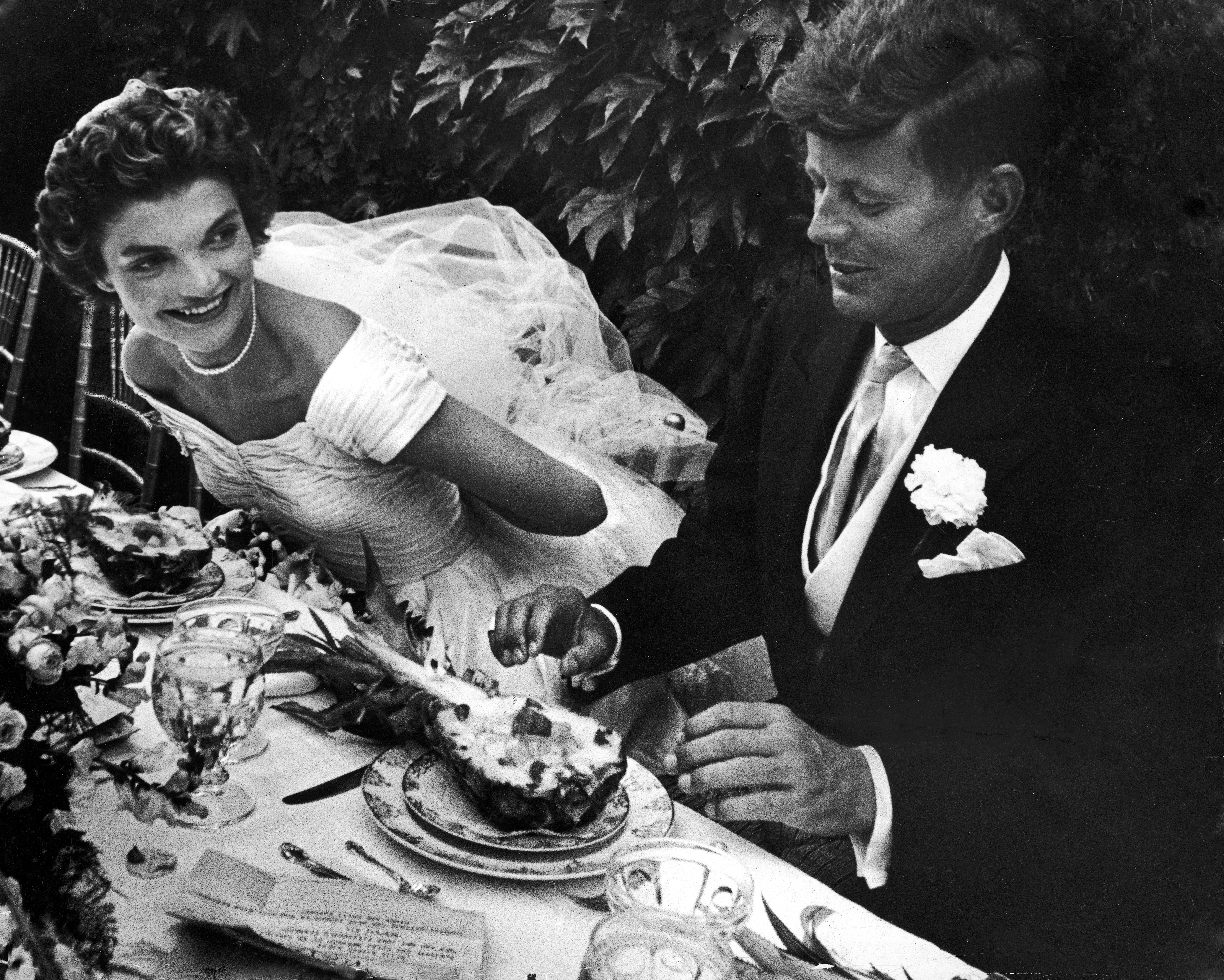 RHODE ISLAND, UNITED STATES - 1953: Senator John Kennedy & his bride Jacqueline in their wedding attire, as they sit down together at table to begin eating a pineapple salad at formally set table outdoors at their wedding reception. (Photo by Lisa Larsen/The LIFE Picture Collection/Getty Images)