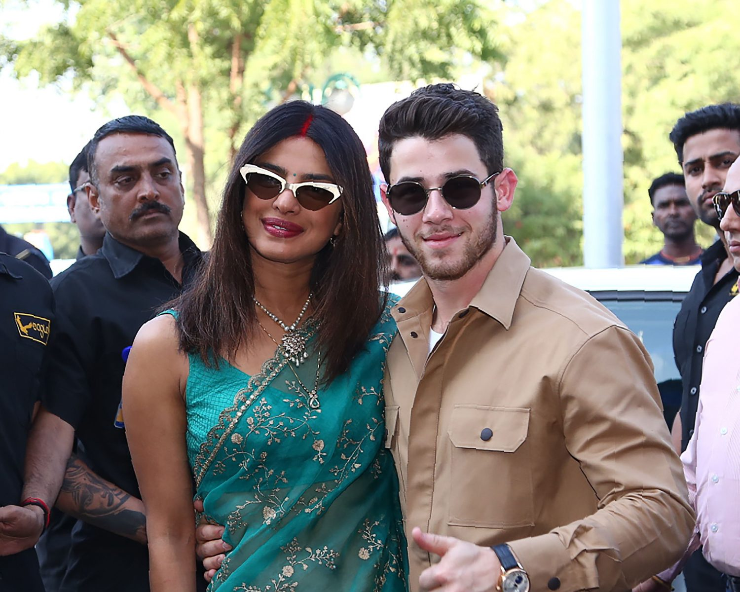 97648eb8e0 Indian Bollywood actress Priyanka Chopra (C) and US musician Nick Jonas  (centre R) pose for a photograph as they leave after their wedding ceremony  in ...