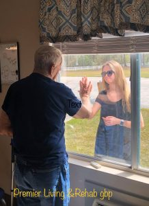 woman showing grandfather engagement through window